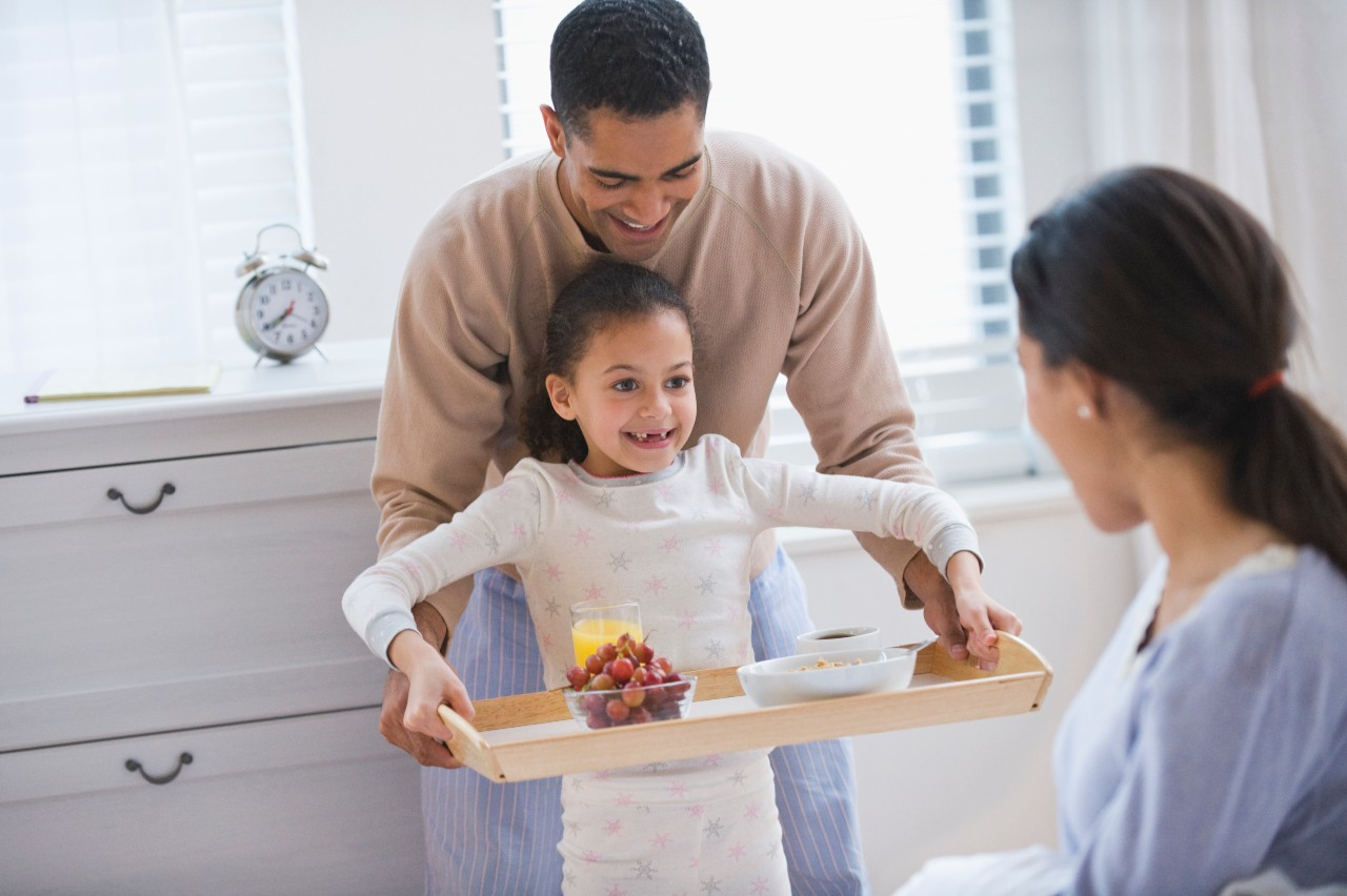 Father and daughter bringing breakfast to mother