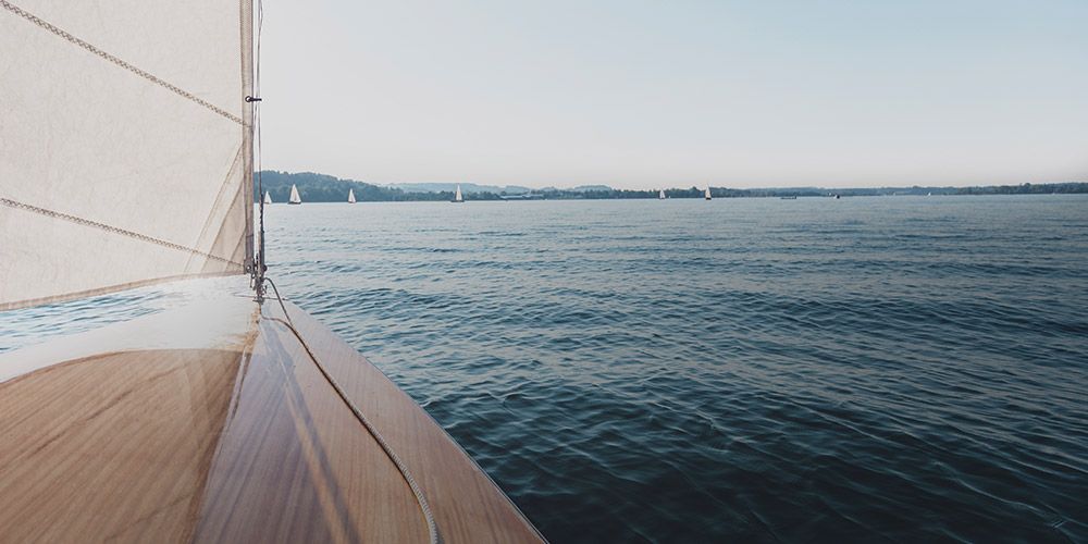 View off water off of  the front of a sailboat.