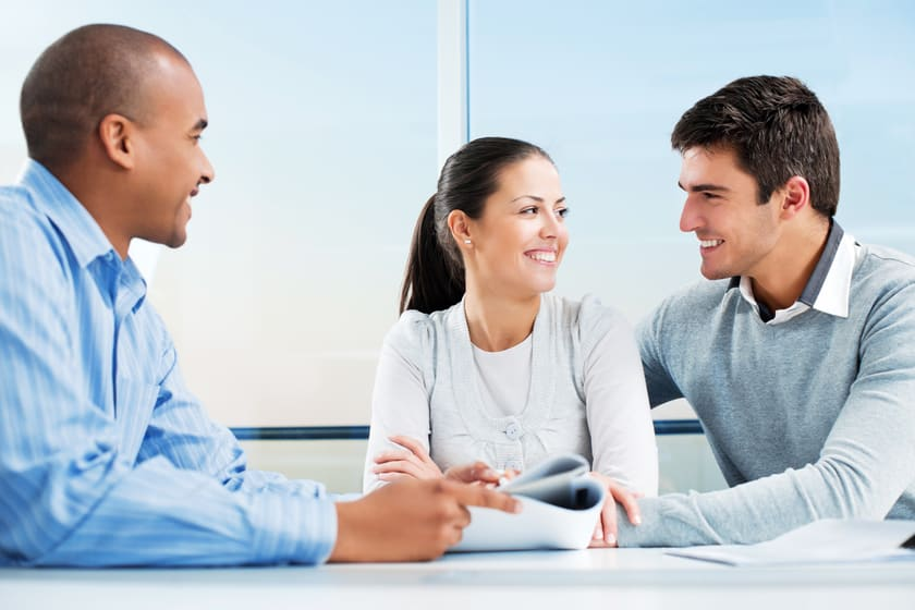 Couple talking to real estate agent and smiling