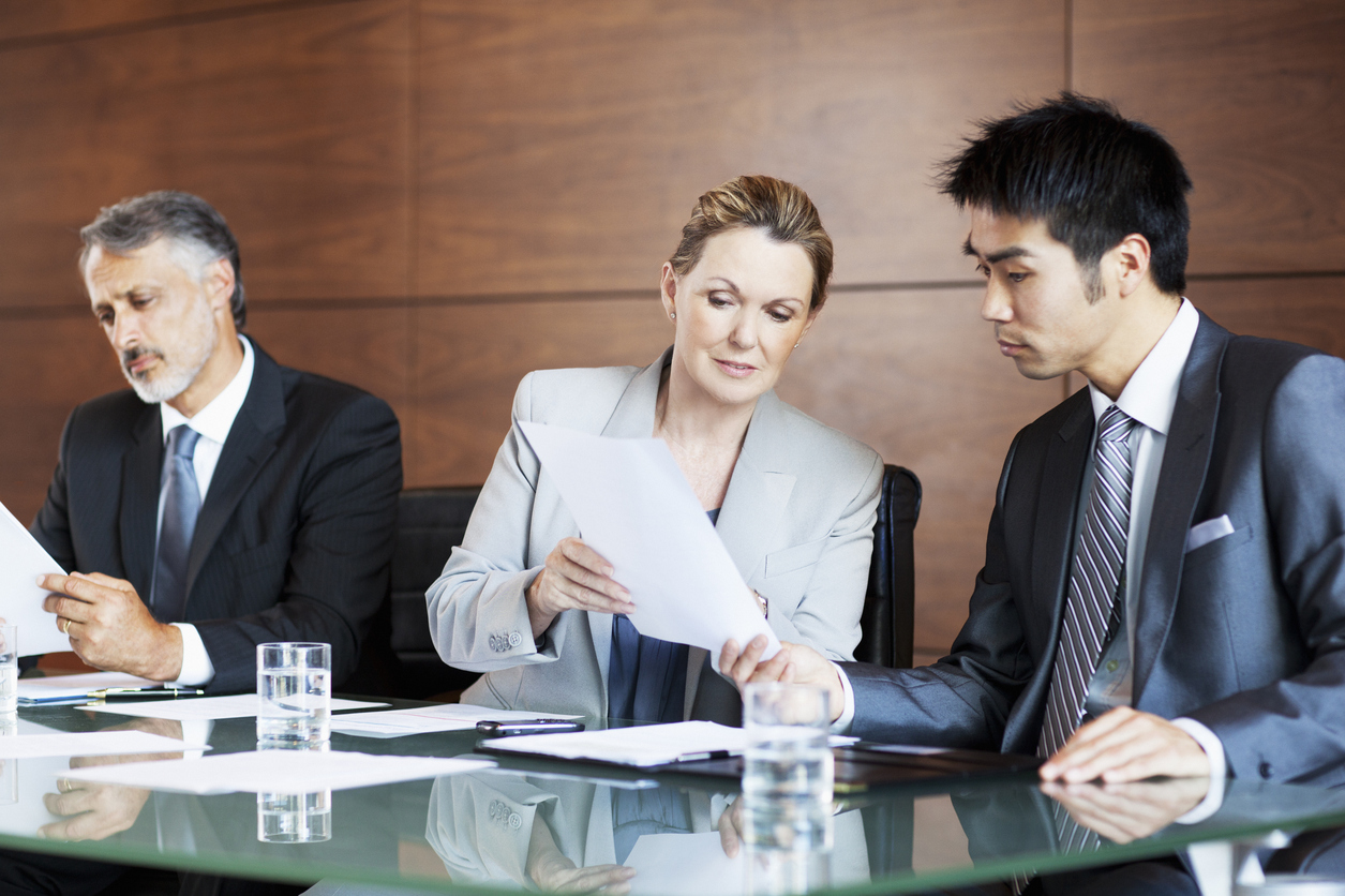 Business executives at a board table discussing equipment financing options