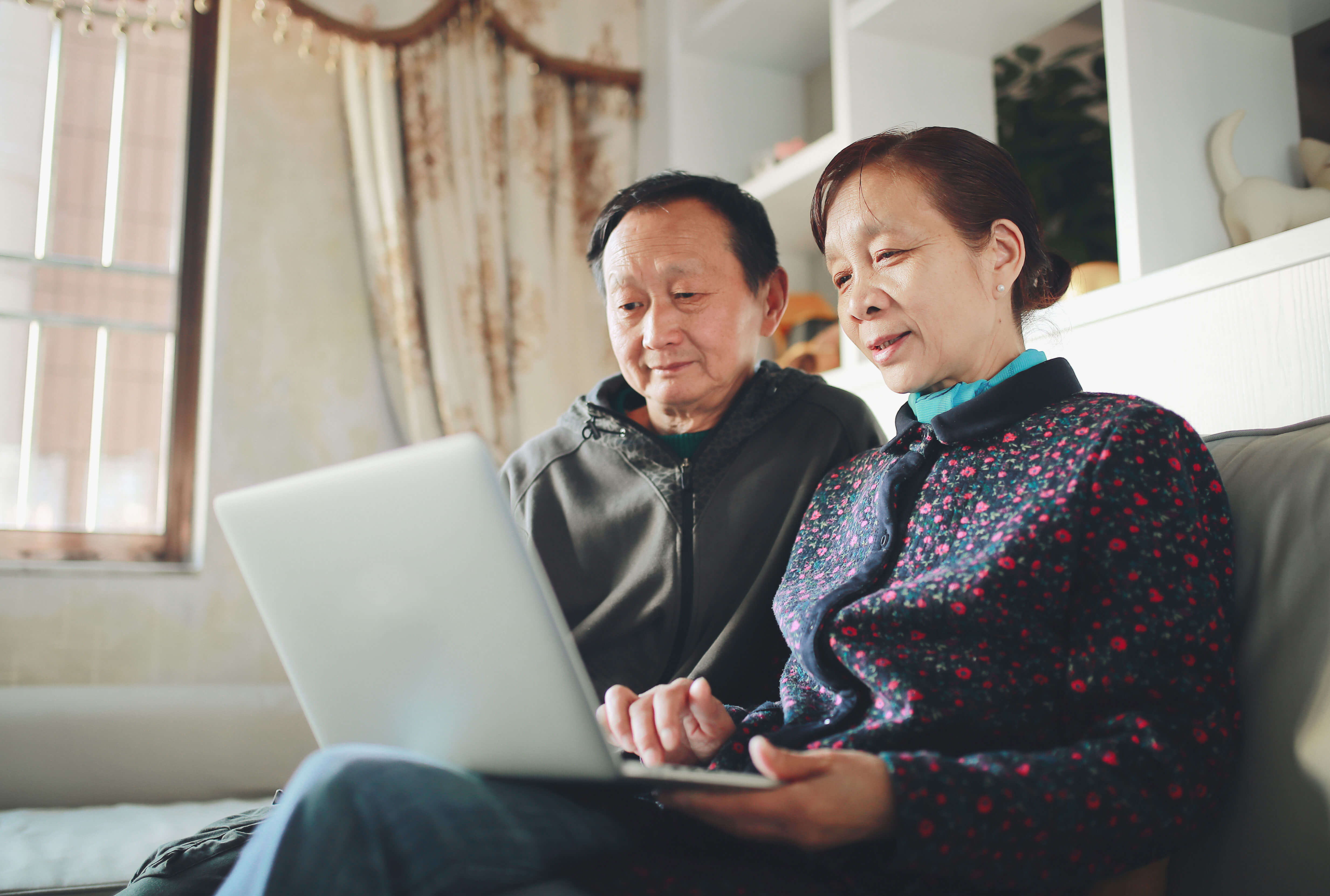 Couple sitting on a couch, using their laptop to help plan their estate