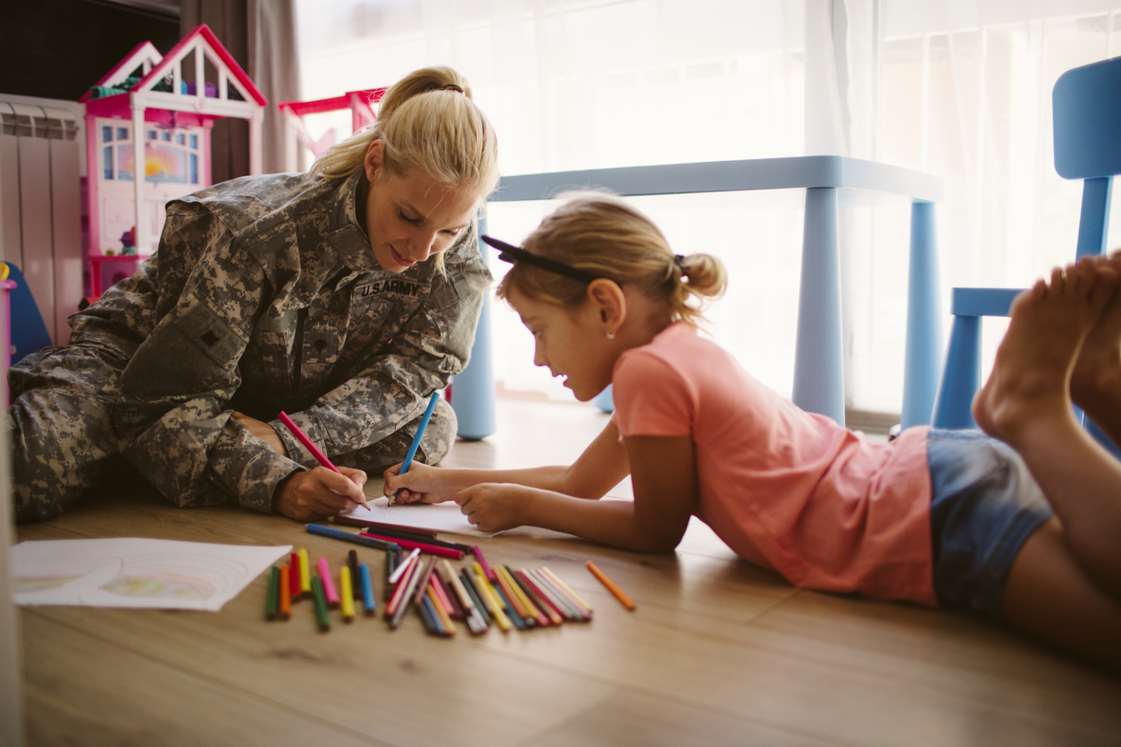 Veteran sitting on the floor with her daughter, coloring