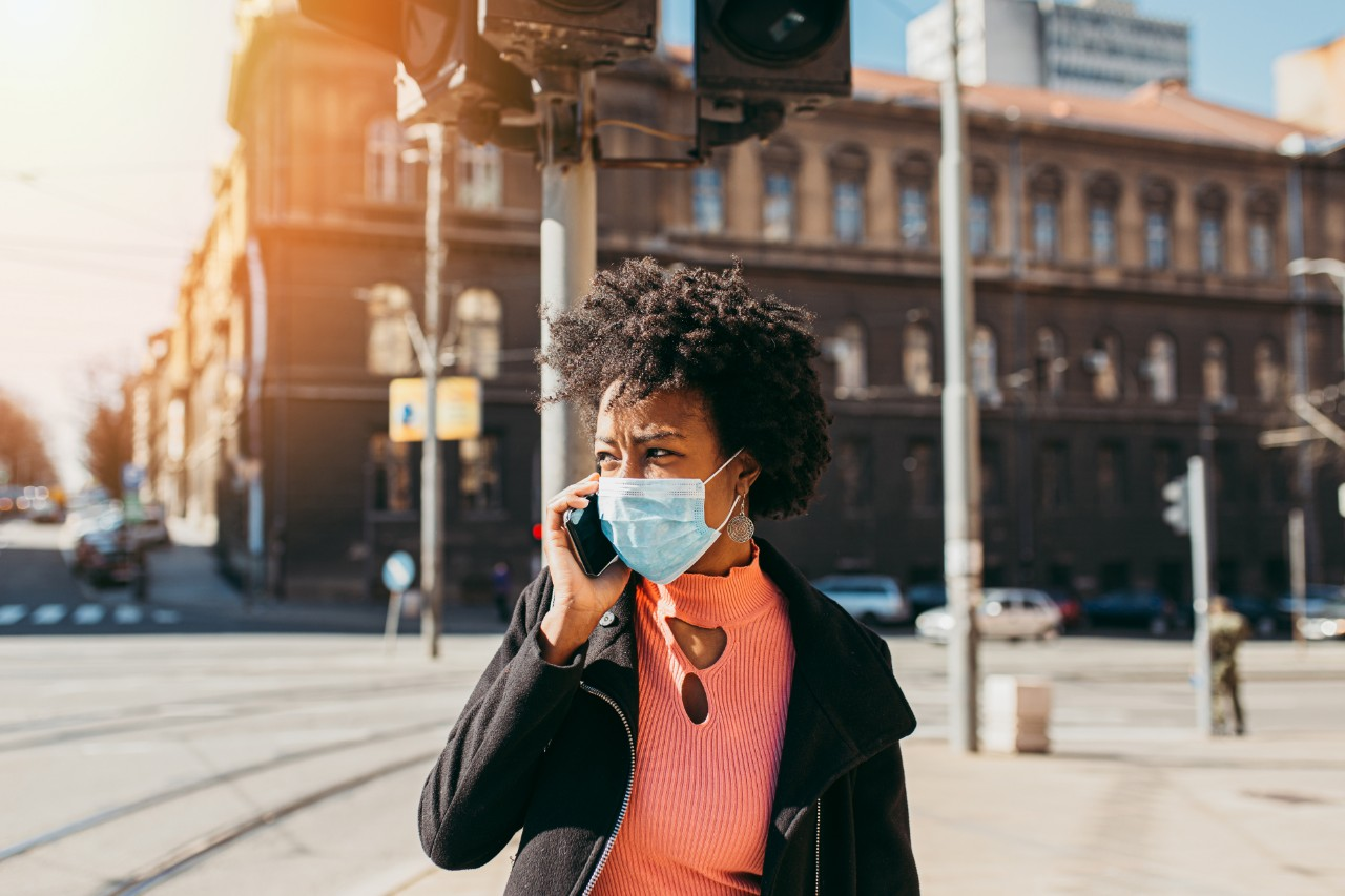 Woman using phone while wearing mask outdoors