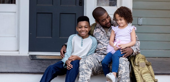 Veteran with children sitting in front of home purchased with VA loan
